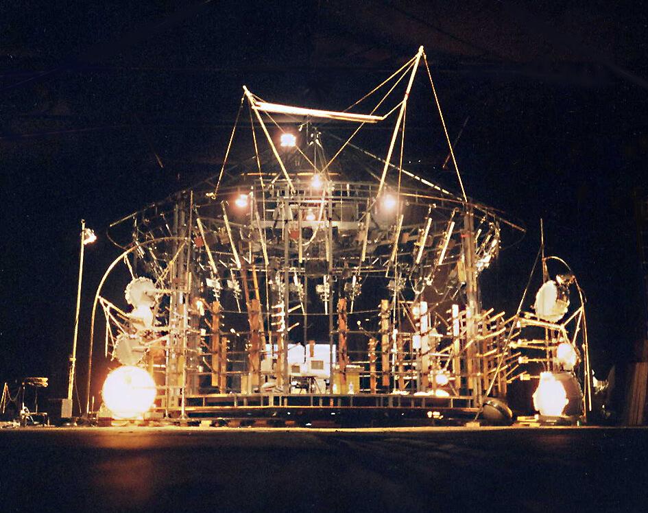 Photographie sur fond noir montrant la structure d'un manège mécanique avec éléments de percussions et carillon tubulaire