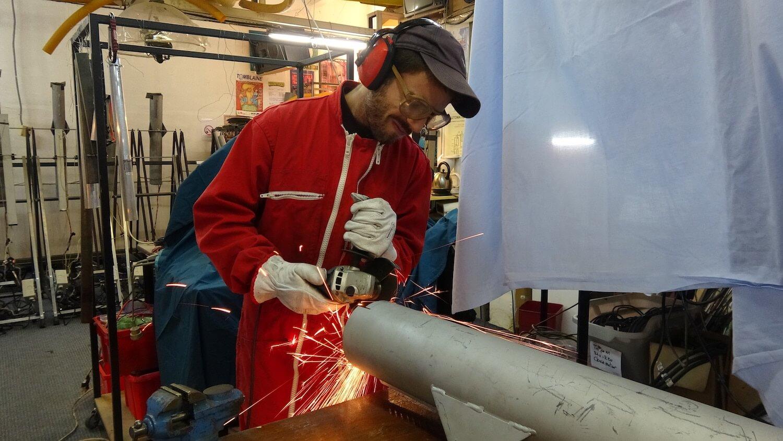 Photographie dans l'atelier : un jeune homme, debout, en combinaison rouge, raccourcit un gros tuyaux en acier.