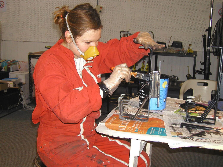 Photographie dans l'atelier : jeune femme en combinaison rouge, avec masque de protection, peint des pièces métalliques,
