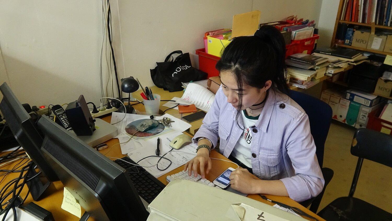 Photographie au bureau de l'atelier : jeune femme devant 3 ordinateurs