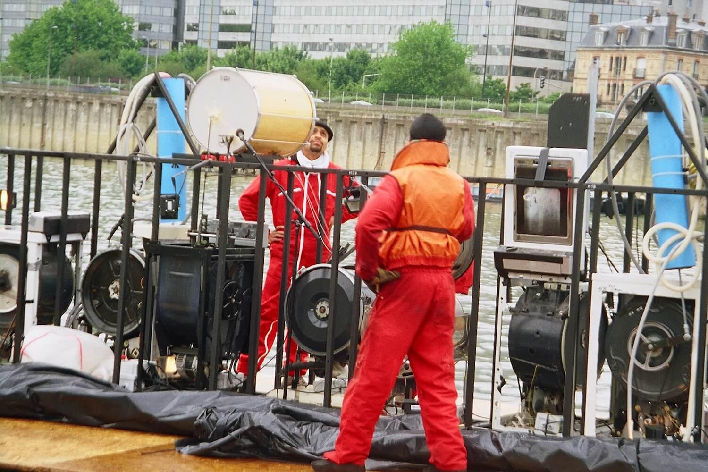 Photographie de l'installation des Machines à laver musicales au bord de l'eau avec deux techniciens en combinaison rouge.