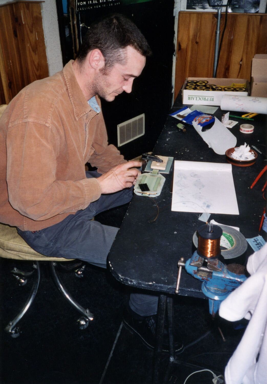 Photographie dans l'atelier : jeune homme à une table d'assemblage et de bobinage,