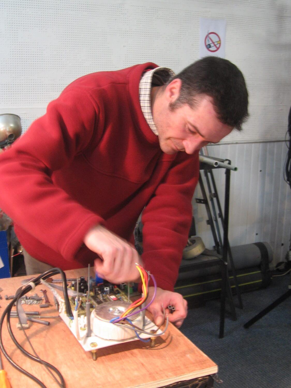 Photographie dans l'atelier : un jeune homme debout procède à un montage électronique.