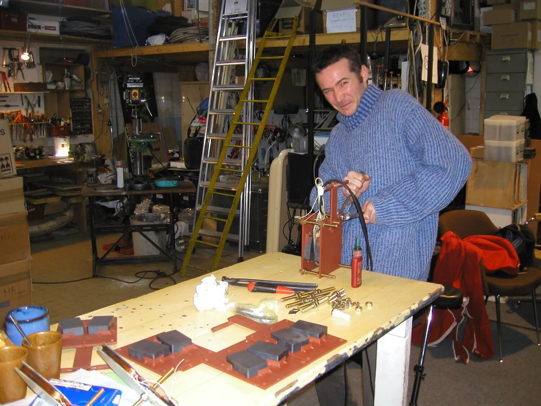 Photographie dans l'atelier : un jeune homme debout procède au serrage de partie de moteur de Carillon