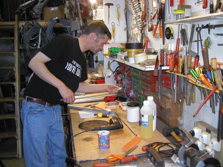 Photographie dans l'atelier : un jeune homme debout se penche sur un établi devant un panneau d'outils