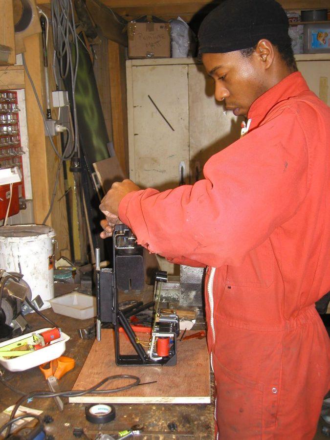 Photographie dans l'atelier : un jeune homme debout, en combinaison rouge assemble un élément de sculpture musicale sonore.