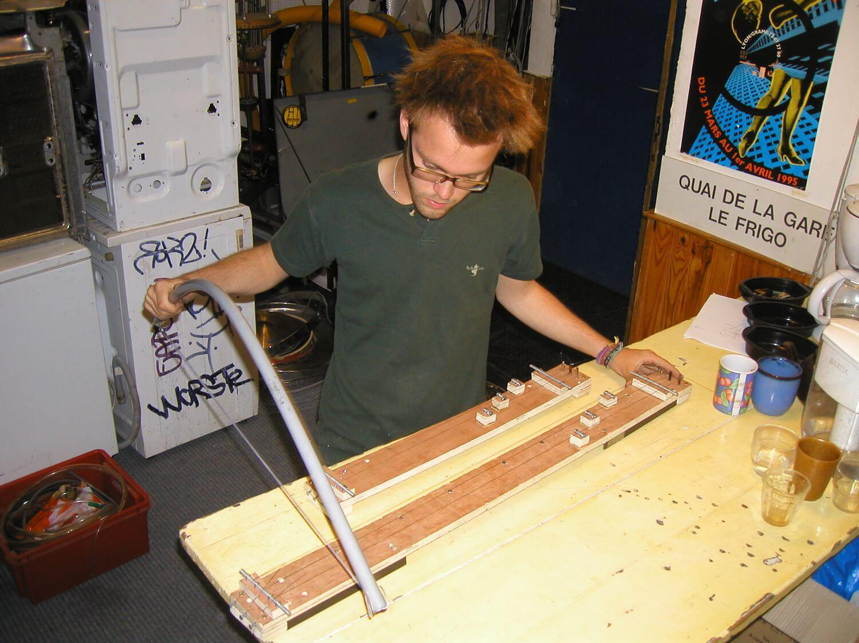 Photographie dans l'atelier : un jeune homme debout, tient un archet en arc et l'essaie sur des cithares sur planche.