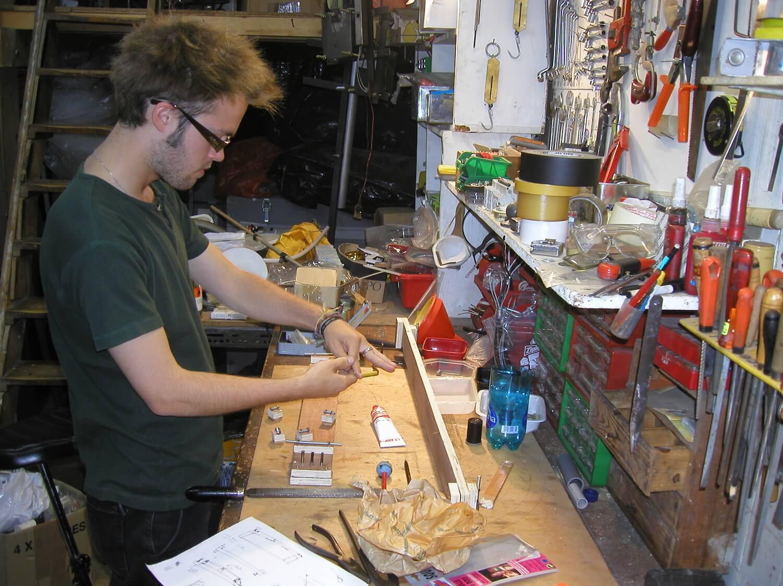 Photographie dans l'atelier : un jeune homme, debout devant un établi dans l'atelier, construit des cithares sur planche.