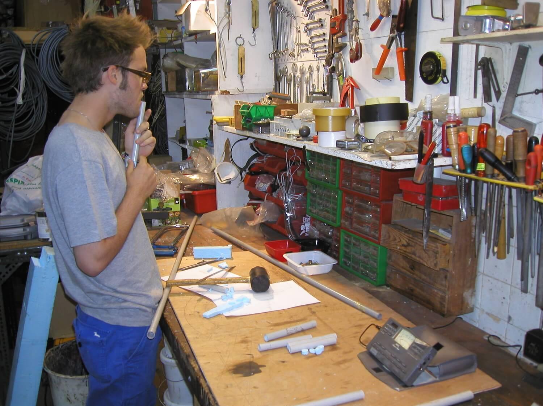 Photographie dans l'atelier : un jeune homme, debout devant un établi dans l'atelier, souffle f-dans un tuyau vertical contrôlant un accordeur électronique.
