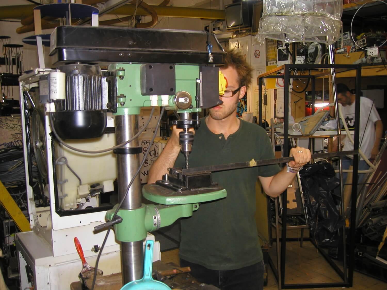Photographie dans l'atelier : un homme utilise une perceuse