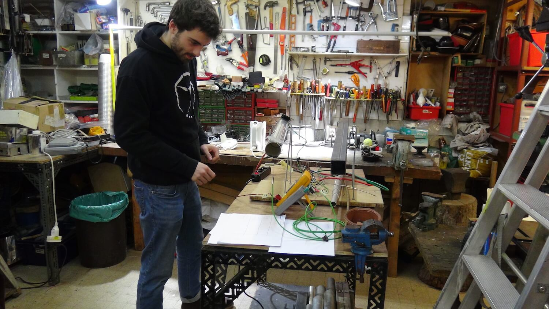 Photographie dans l'atelier : un jeune homme, debout devant un banc d'essai sur fond d'établi avec panneau d'outils