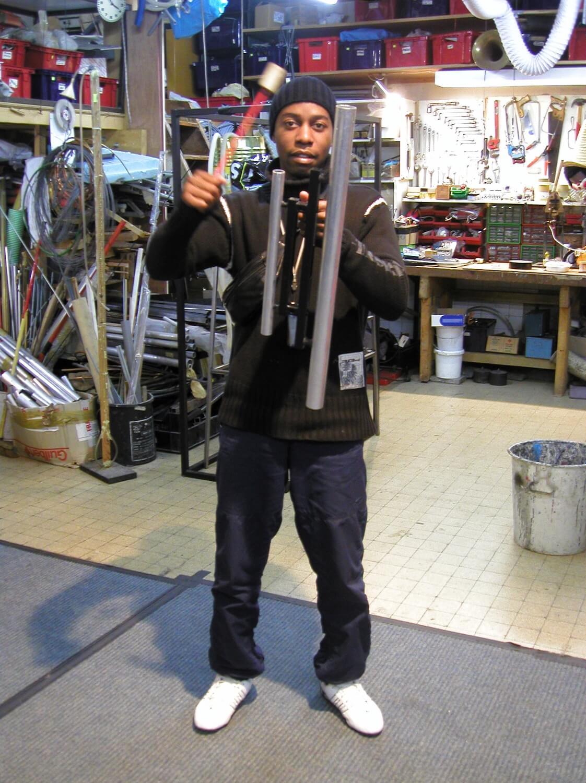 Photographie dans l'atelier : un jeune homme, debout, frappe un double carillon tubulaire tenu à la main