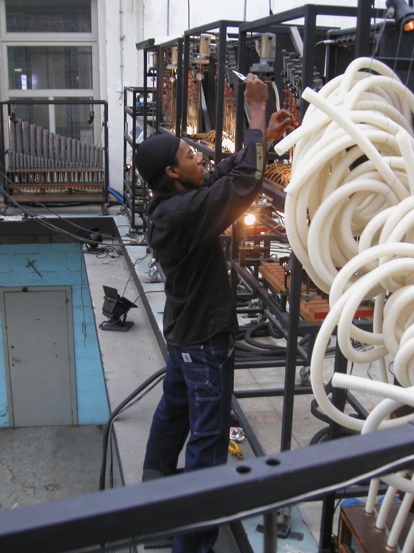 Photographie dans l'atelier : un jeune homme, debout devant les machines, tient un outil et une corde