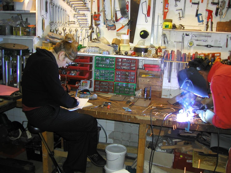 Photographie dans l'atelier : une jeune femme sur un tabouret rédige un document et, à droite, un jeune homme soude à l'arc