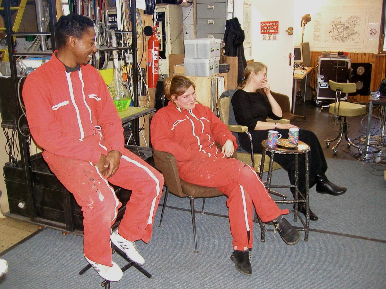 Photographie dans l'atelier : deux jeunes femmes et un jeune homme , assis , rigolent