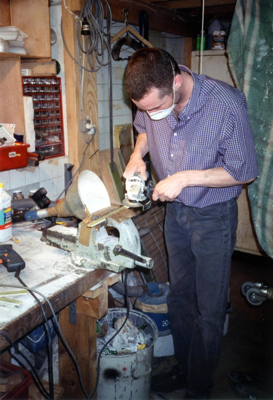 Photographie dans l'atelier : un jeune homme, debout, manipule un outil au dessus d'un étau.