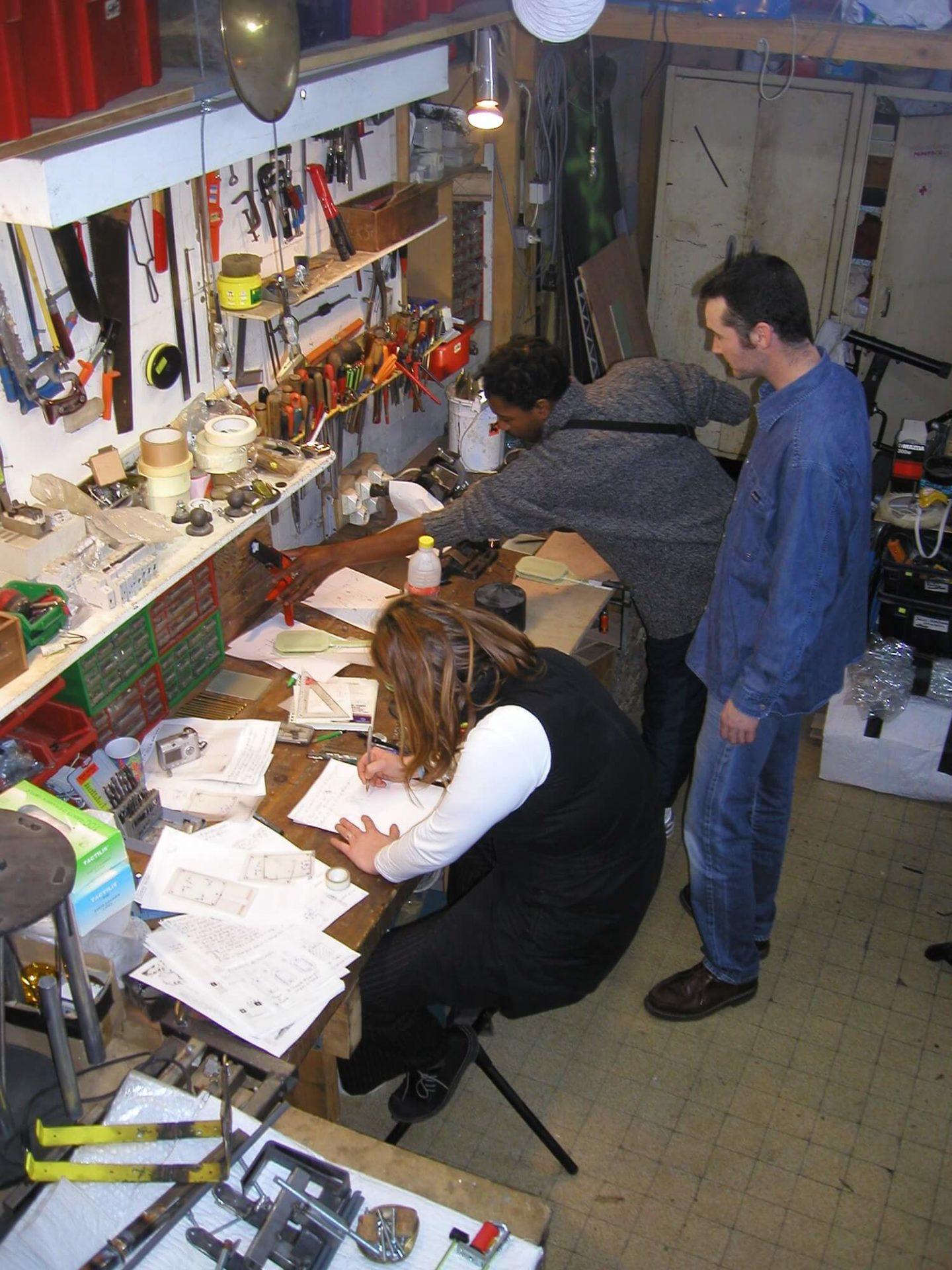Photographie dans l'atelier : sur un établi une jeune femme écrit, un jeune homme attrape un outil , un deuxième le conseille