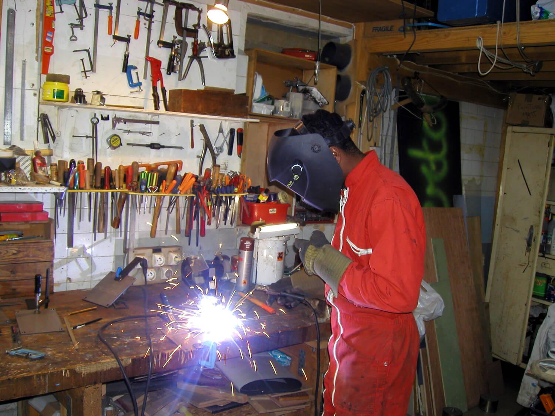 Photographie dans l'atelier : un jeune homme en combinaison rouge, muni de gros gants et d'un casque électronique soude à l'arc, lumière vive.