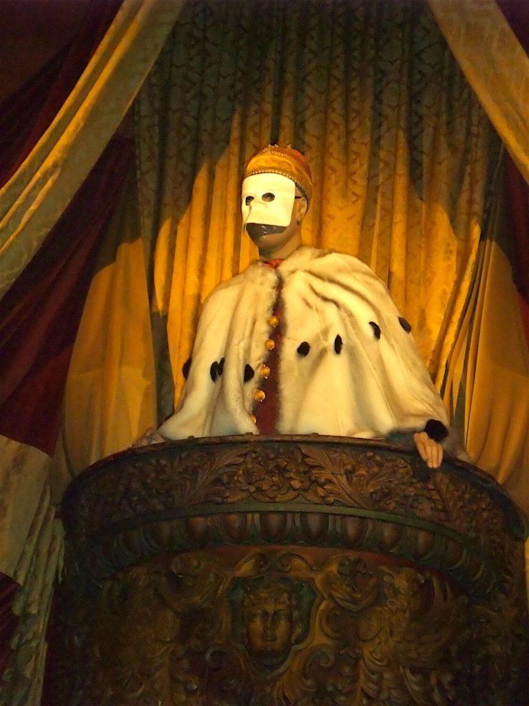 Photographie: dans un balcon entouré de draperies, personnage masqué avec cape de fourrure blanche