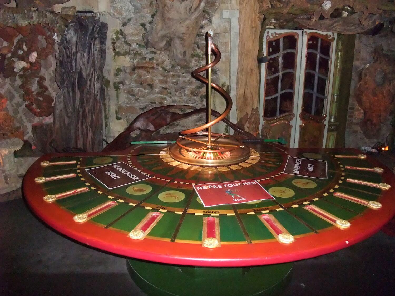 Photographie: table semi circulaire avec palets glissants sur les signes du zodiaque, au centre une roulette de casino avec un serpent en cuivre
