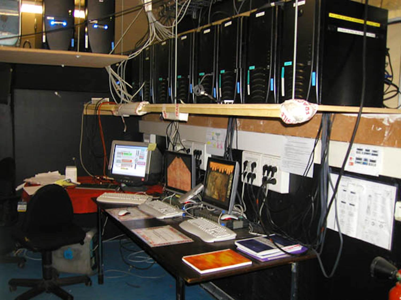 Photographie: table et étagères avec écrans et unités centrales d'ordinateurs