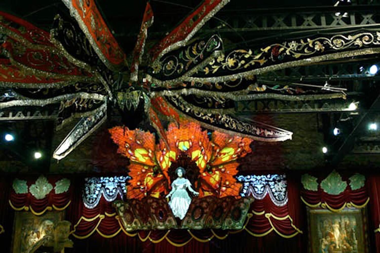 Photographie: décors lumineux dans la pénombre, personnage entouré d'ailes de papillon