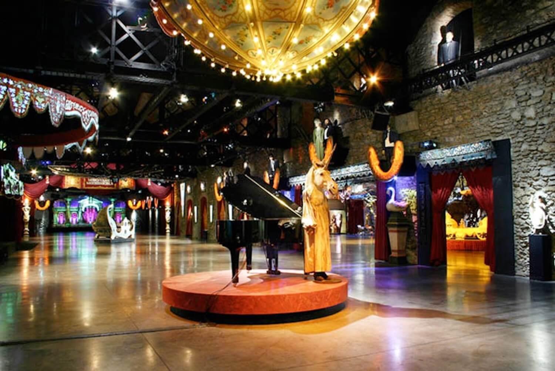 Photographie: grande salle avec lumières muséographique, piano à queue et Licorne au milieu