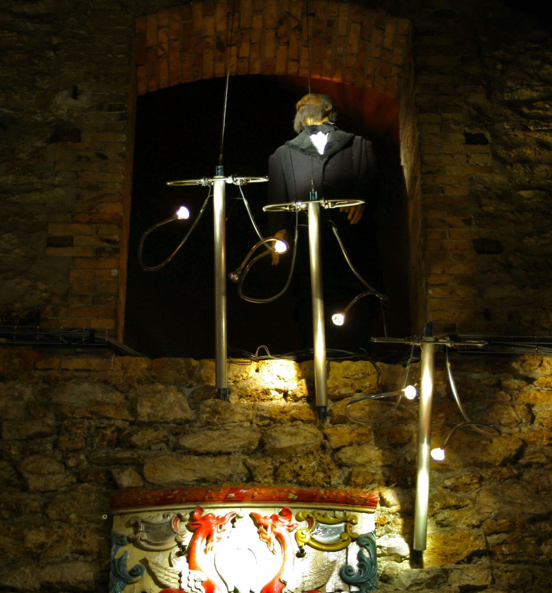 Photographie: dans la pénombre sur un mur 3 carillons tubulaires avec leurs lumières devant un personnage en cire