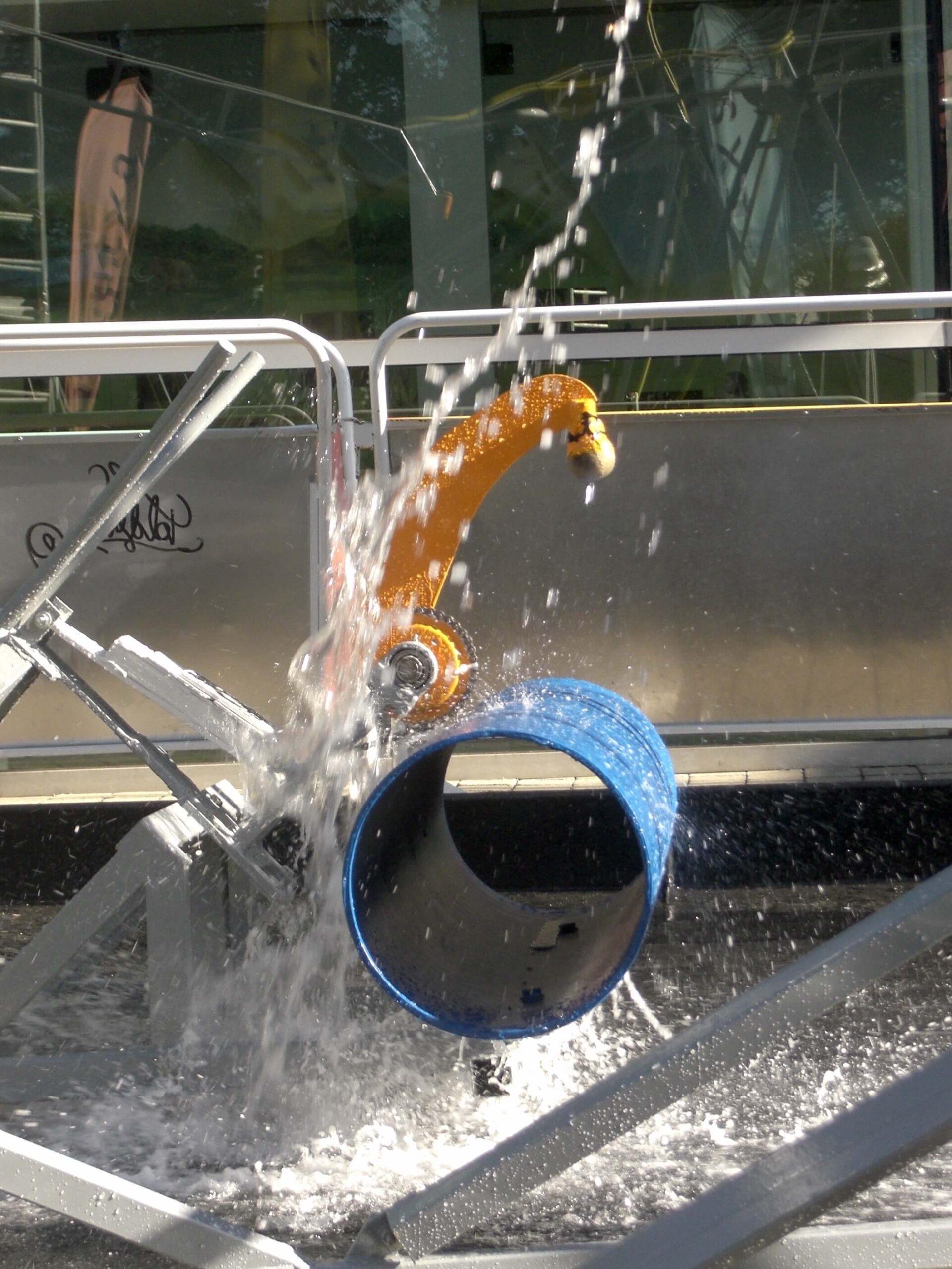 Photographie d'un détail d'une machine sonore hydraulique en action, dans un bassin d'eau, marteau orange actionnant un bras s de même couleur frappant sur un cylindre bleu.