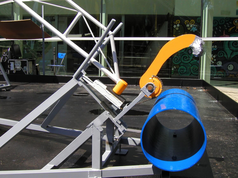 Photographie d'un détail d'une machine sonore hydraulique dans un bassin d'eau, marteau orange actionnant un bras s de même couleur frappant sur un cylindre bleu.