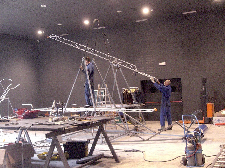 Photographie montrant deux hommes dans un grand hangar qui assemblent des structures métalliques , en premier plan des éléments de l'atelier de construction
