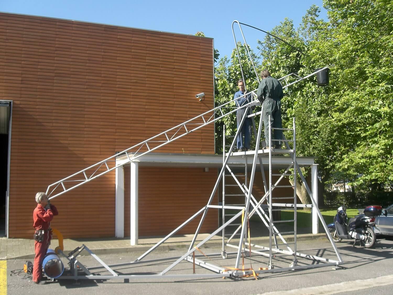 Photographie montrant deux hommes perchés sur un échafaudage. Ils assemblent des structures métalliques d'une des grandes bascules à percussions,en second plan un bâtiment en brique et un grand arbre.