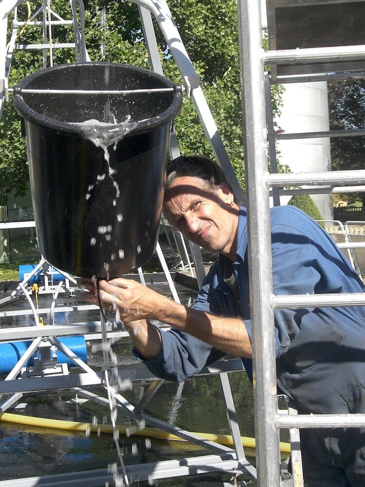 Photographie: un homme en bleu de travail ajusteur récipient noir contenant de l'eau, en arrière plan des éléments des sculptures sonores , en premier plan une échelle.