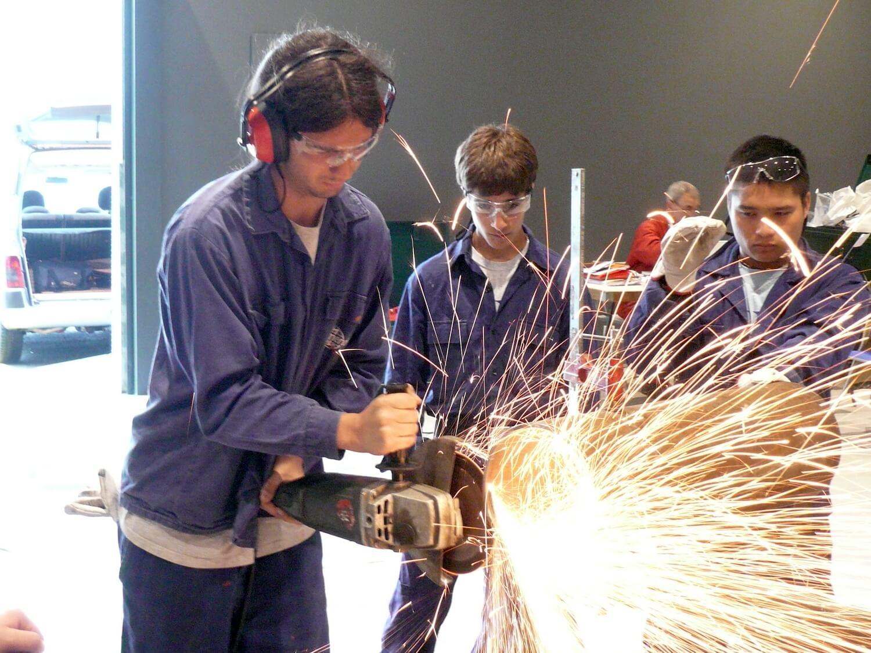 Dans un grand hangar 2 adolescents en bleu de travail un troisième manipulant une tronçonneuse dans un nuage d'étoincelles