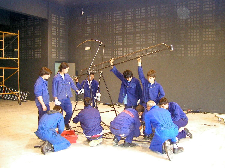 Dans un grand hangar 9 adolescents en bleu de travail regardent avec un adulte le fonctionnement d'une machine métallique à allure squelettique