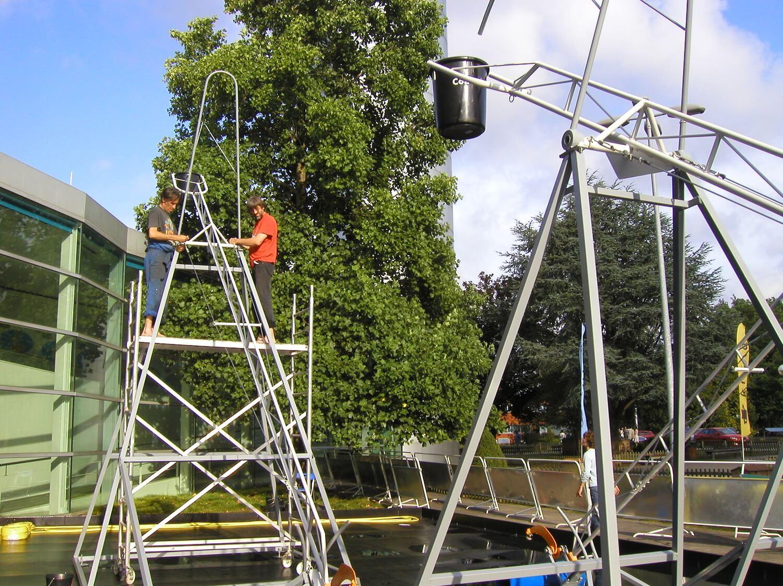 Photographie montrant deux hommes perchés sur un échafaudage et assemblant des structures métalliques , en premier plan des éléments d'une autre structure, en second plan un grand arbre.