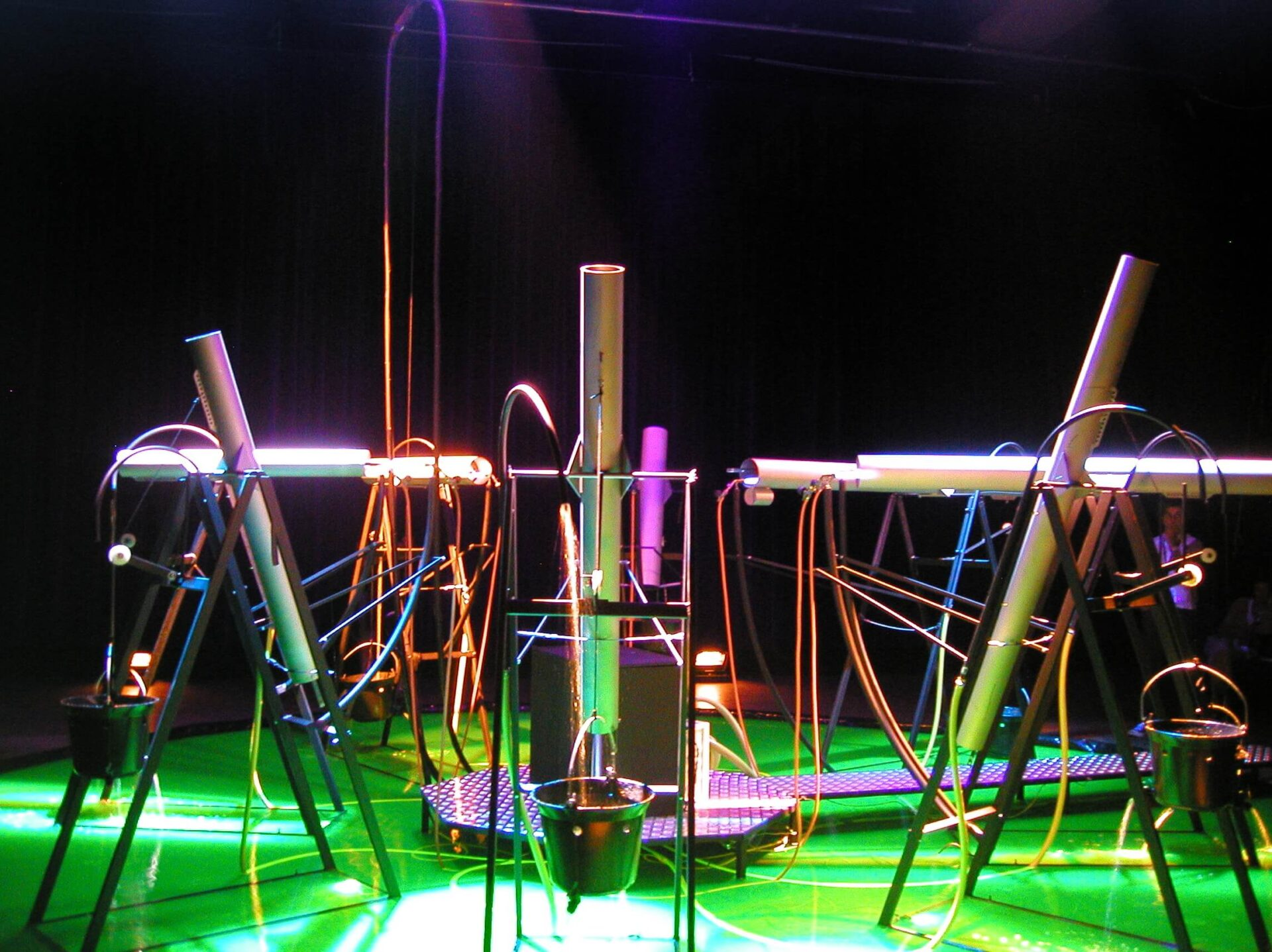 Photographie montrant des tuyaux montés sur châssis , évoquant de gros mortiers militaires, au dessus d'une surface vert fluorescent ,sur un fond noir . Lumières de spectacle