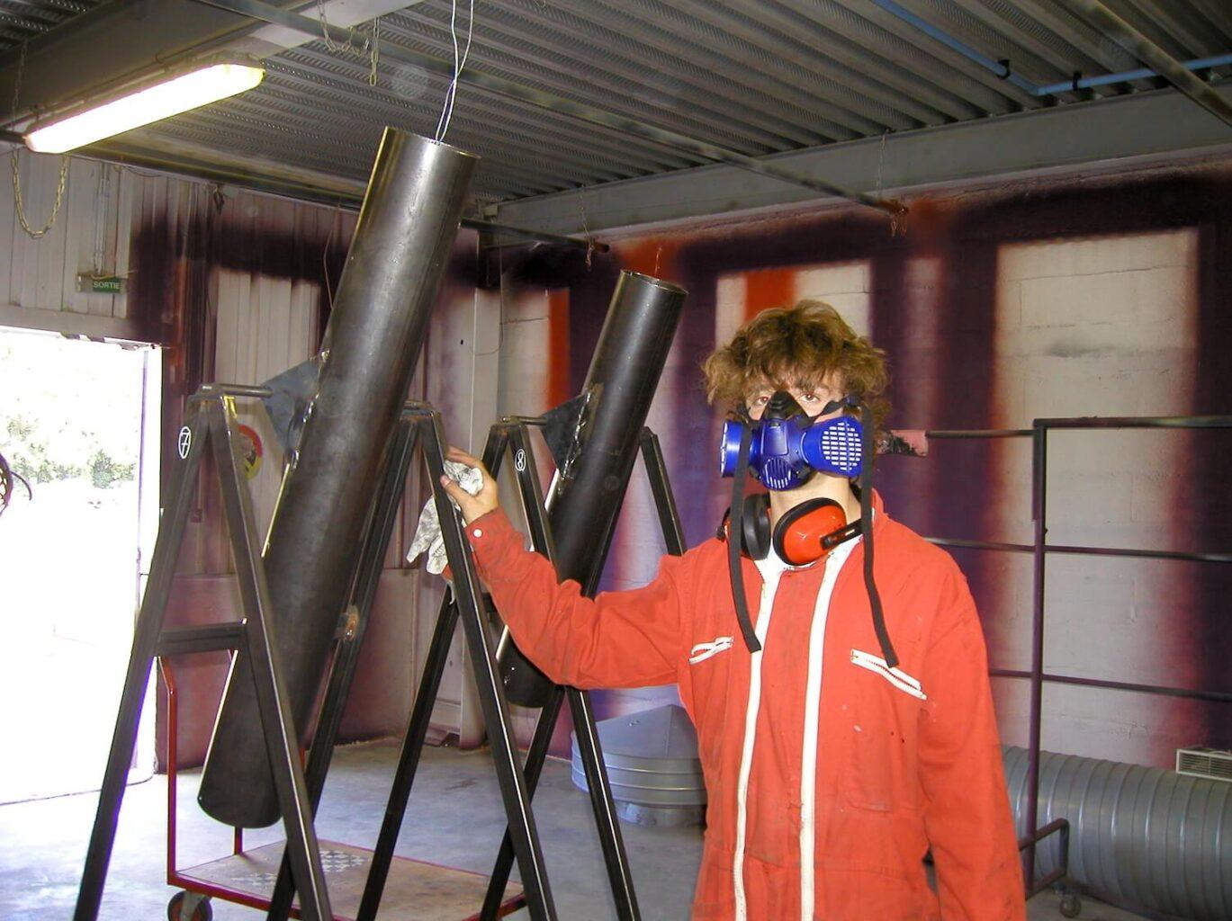 Photographie dans un hangar un jeune homme en combinaison rouge aves un masque de sécurité et un casque anti-bruit s'apprète à nettoyer des tubes métallique sur châssis
