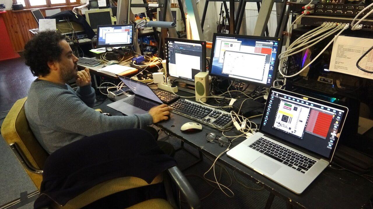 Photographie : homme assis devant plusieurs écrans d'ordinateurs