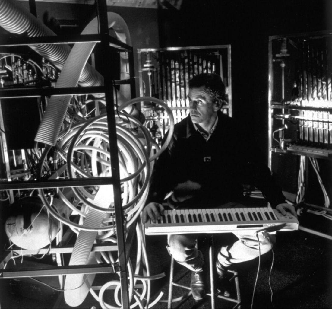 Photographie noir et blanc homme avec clavier de musique , entouré de machines musicales