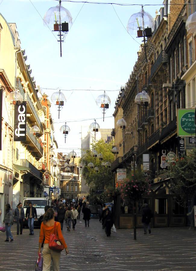 Photographie, public dans rue piétonne sous les barre avec boitiers, suspendues sous leurs coupelles transparentes