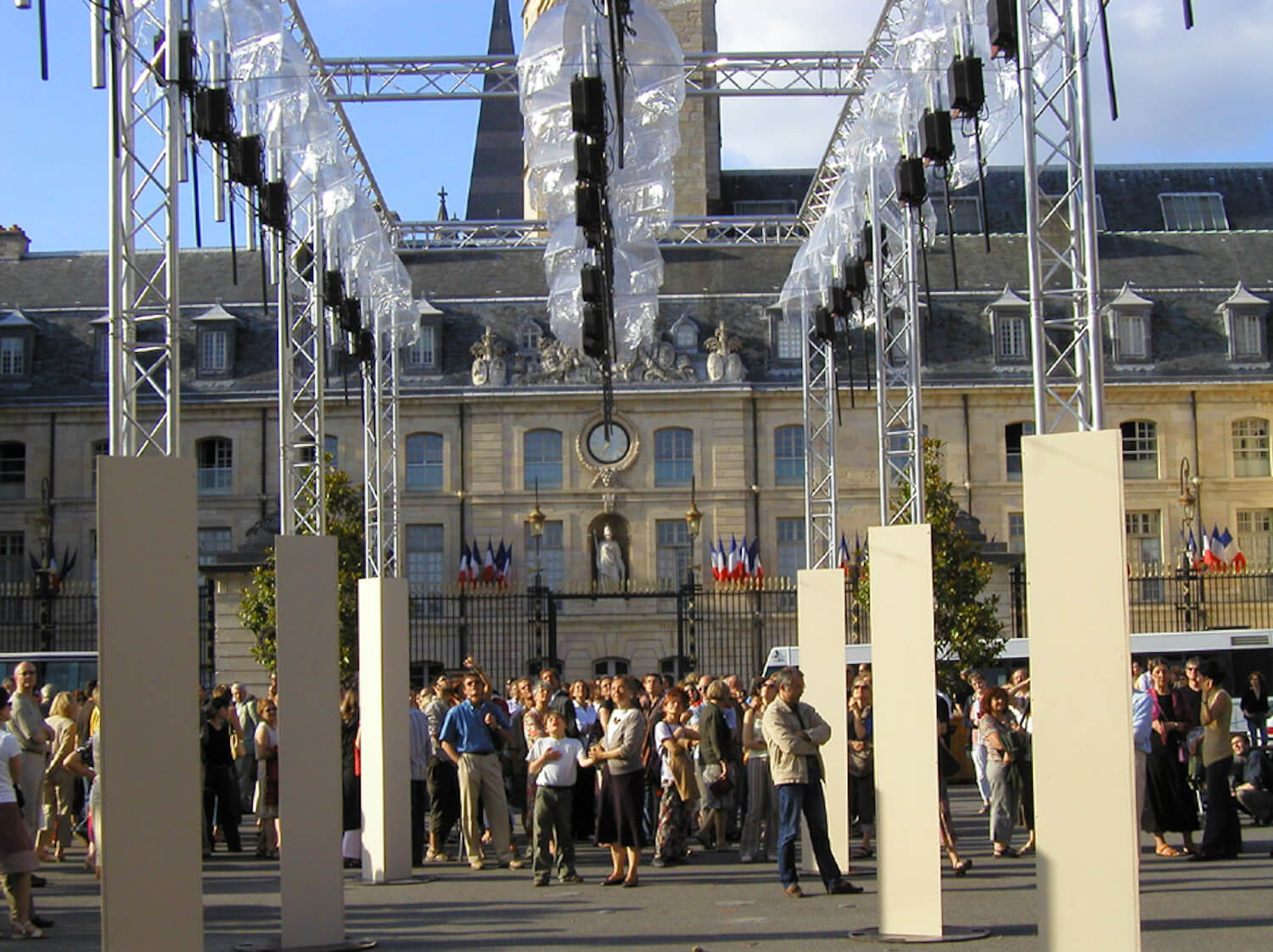 Photo montrant public les yeux en l'air regardant une installation en plein air de machines suspendues
