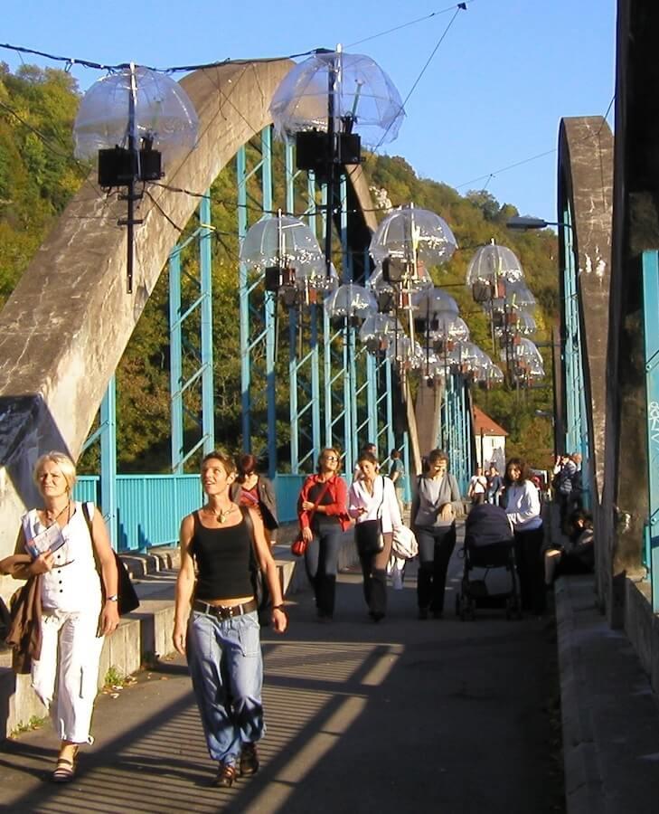 Photographie public sous nombreuses barres avec 2 boitiers suspendues sur un pont sous des parapluies