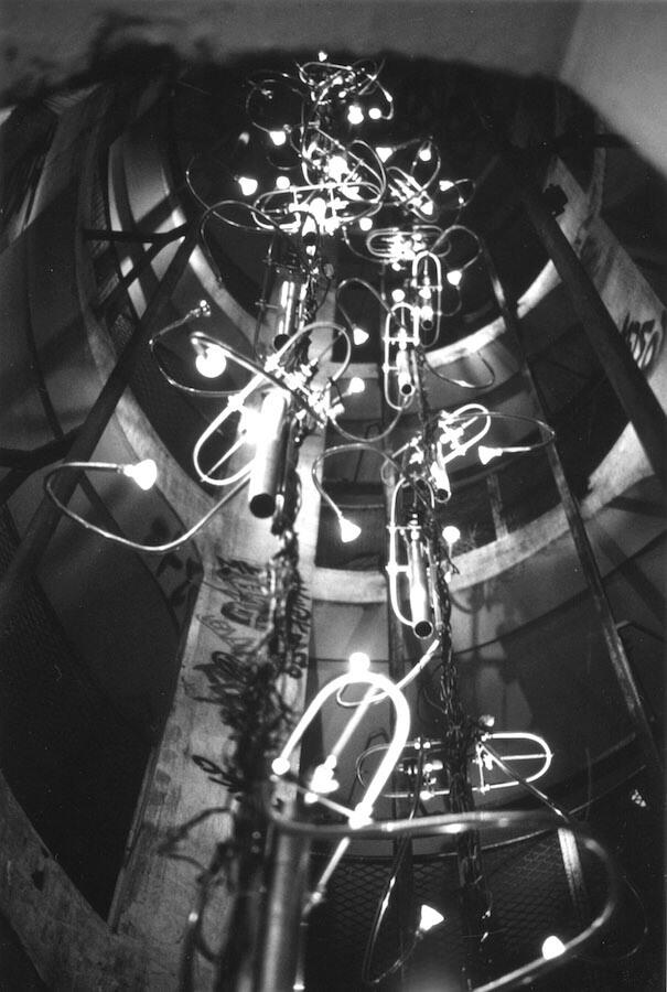 Photographie Noir et Blanc : à l'intérieur d'une tour, des tubes suspendus avec ds bras et des lumières
