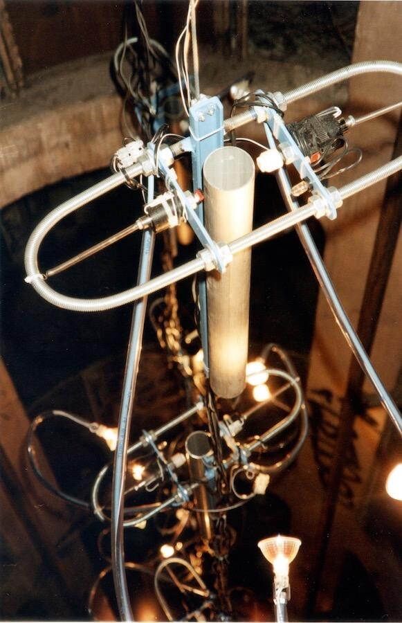 Photographie couleur : tube avec système de percussion à sa tête, suspendu dans le vide et suivi de nombreux autres à l'intérieur d'une tour, des tubes suspendus avec ds bras et des lumières