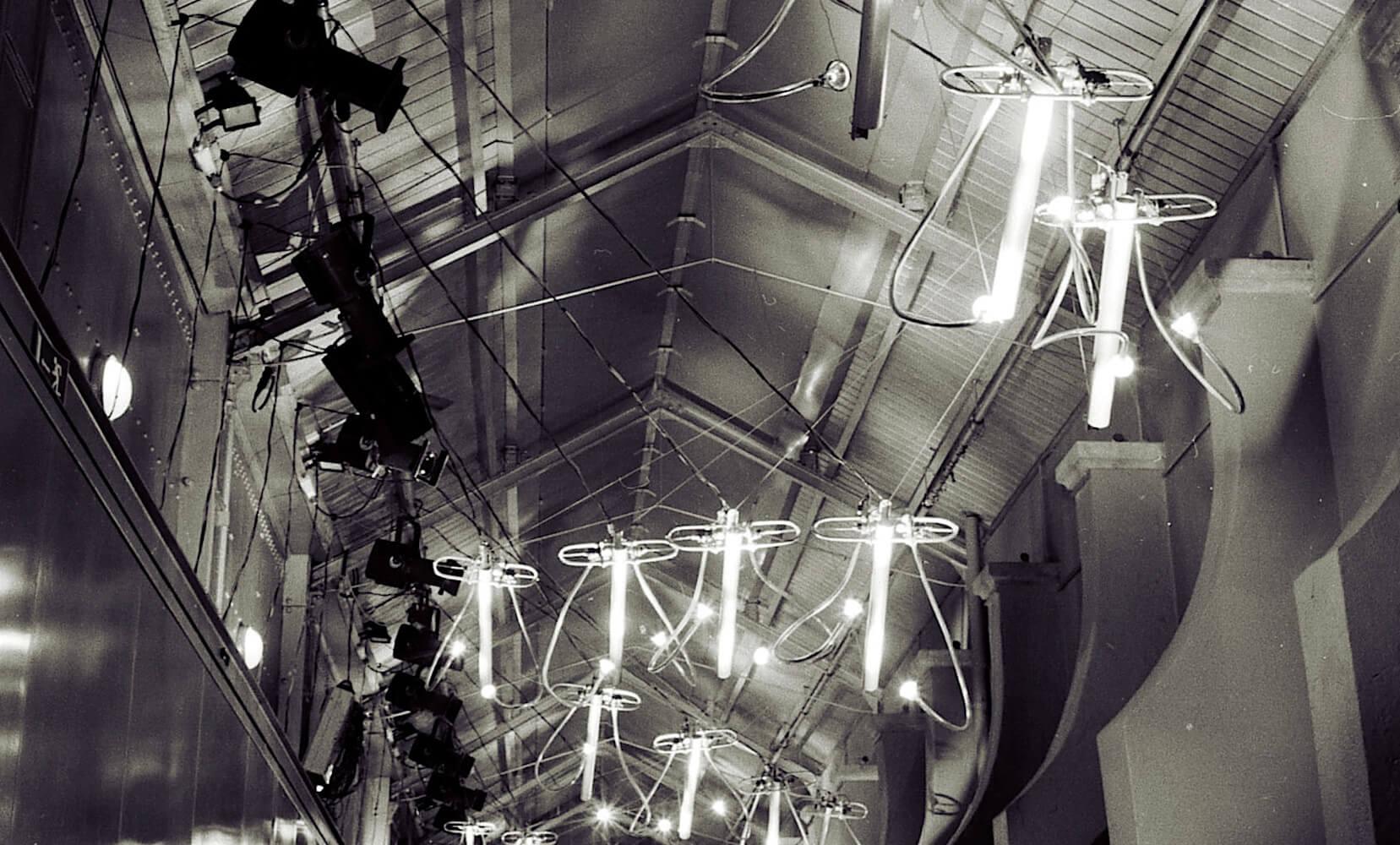 Photographie Noir et blanc : carillons tubulaires suspendus en forme de vol d'oiseaux sous une voute