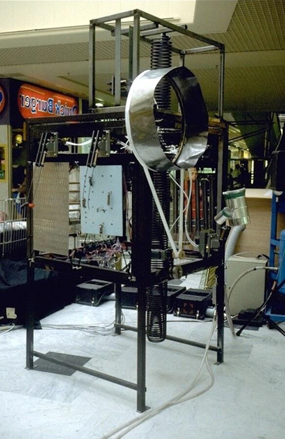 Photographie stand carré avec plaques suspendues, roue métallique et bande blanche et grand ressort