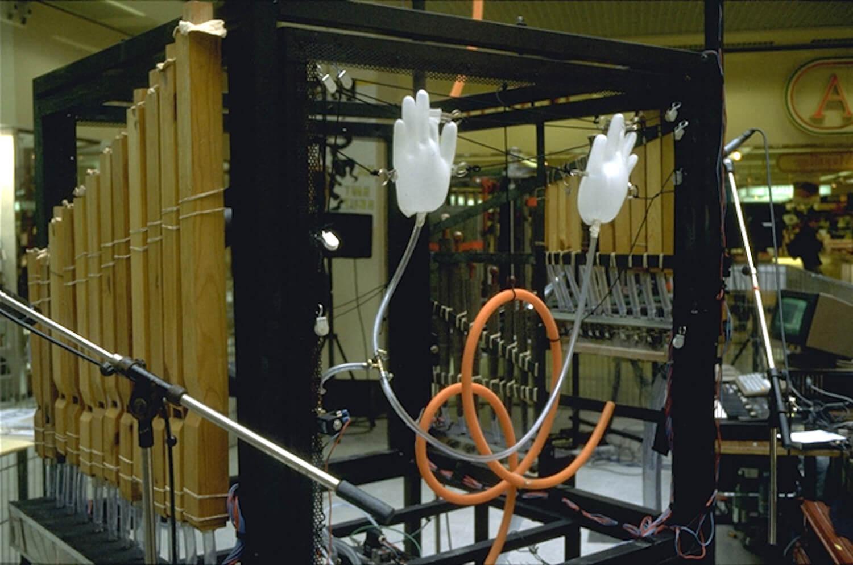 Photographie montrant des tuyaux enlacés se terminant par une paire de gants en latex gonflés