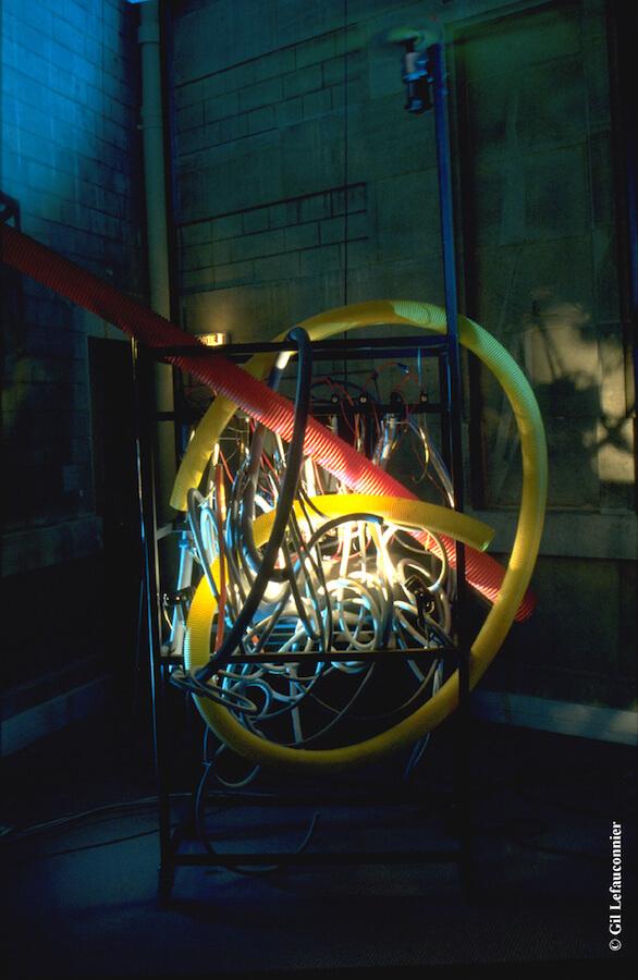 Photographie dans l'obscurité, machine avec nombreux tuyaux colorés, emmêlés et éclairés