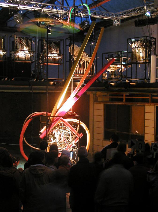 Photographique : public devant machine à tuyaux avec une demi-douzaine de machines en balcon